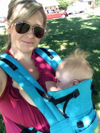 Woman carrying baby in a carrier.  Bonding and attachment with or without breastfeeding